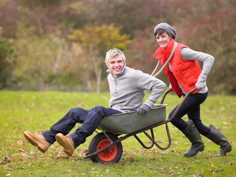 Junge Paare, die in der Schubkarre spielen stockbild