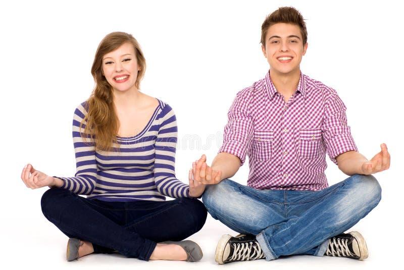 Junge Paare, die in der Yogahaltung sitzen stockbild
