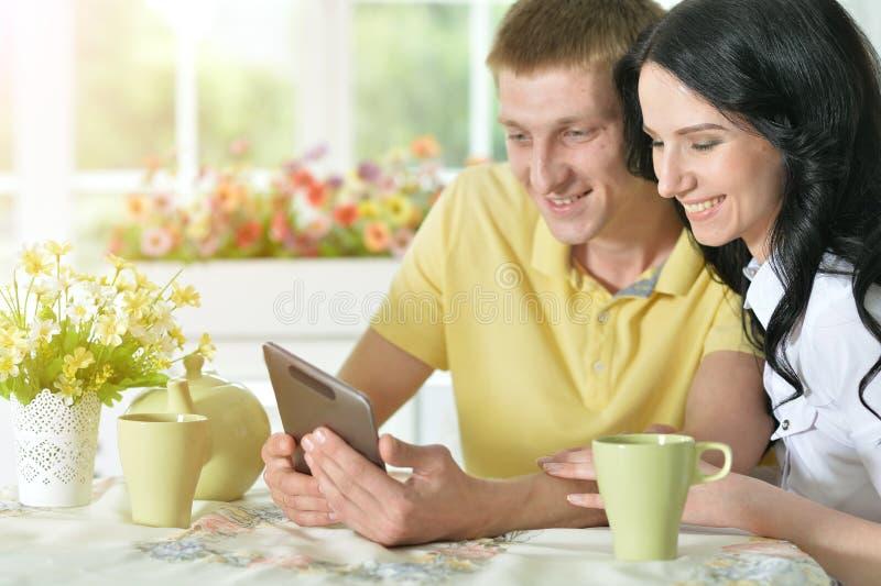 Junge Paare, die digitale Tablette betrachten stockfotos