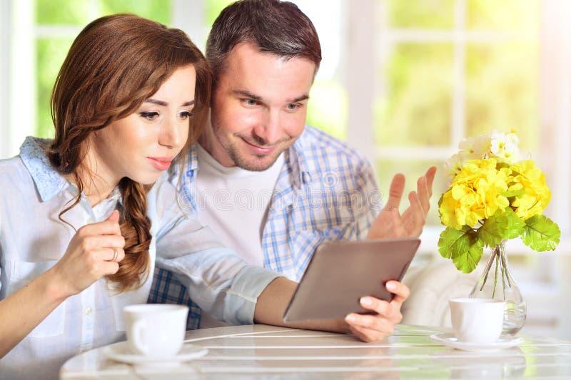 Junge Paare, die digitale Tablette betrachten lizenzfreies stockbild