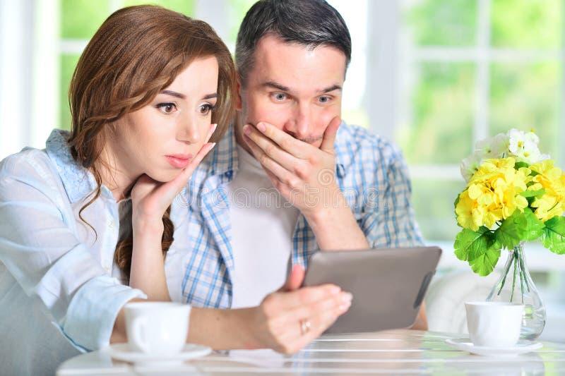 Junge Paare, die digitale Tablette betrachten stockfoto