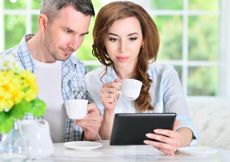 Junge Paare, die digitale Tablette betrachten lizenzfreie stockfotografie