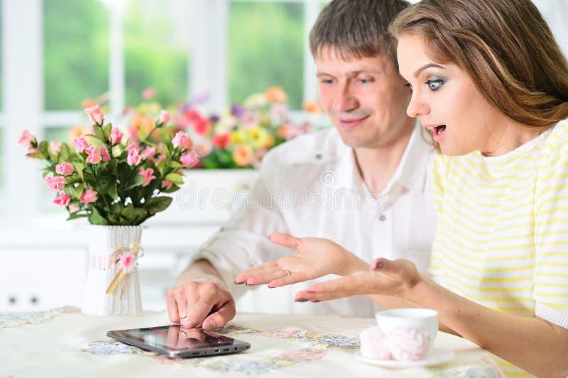 Junge Paare, die digitale Tablette betrachten lizenzfreie stockbilder