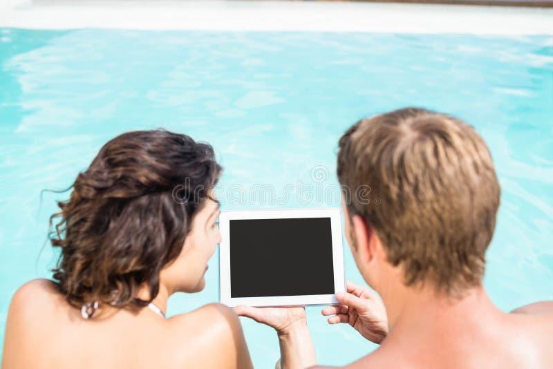 Junge Paare, die digitale Tablette durch Poolside betrachten stockfotos