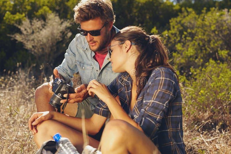 Junge Paare, die draußen Bilder auf Digitalkamera betrachten lizenzfreie stockbilder