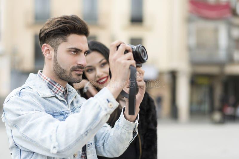 Junge Paare, die draußen Fotos in der Stadt machen stockbilder