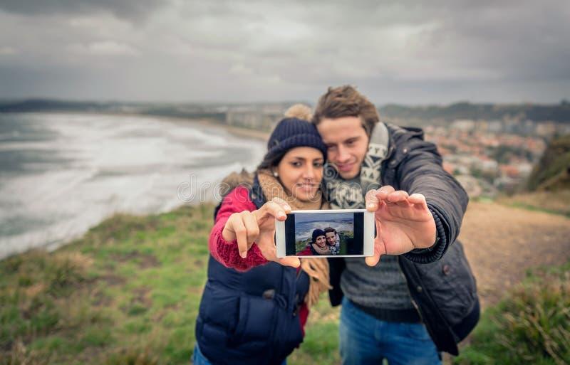 Junge Paare, die draußen selfie Foto mit Smartphone an einem kalten Tag machen lizenzfreies stockbild