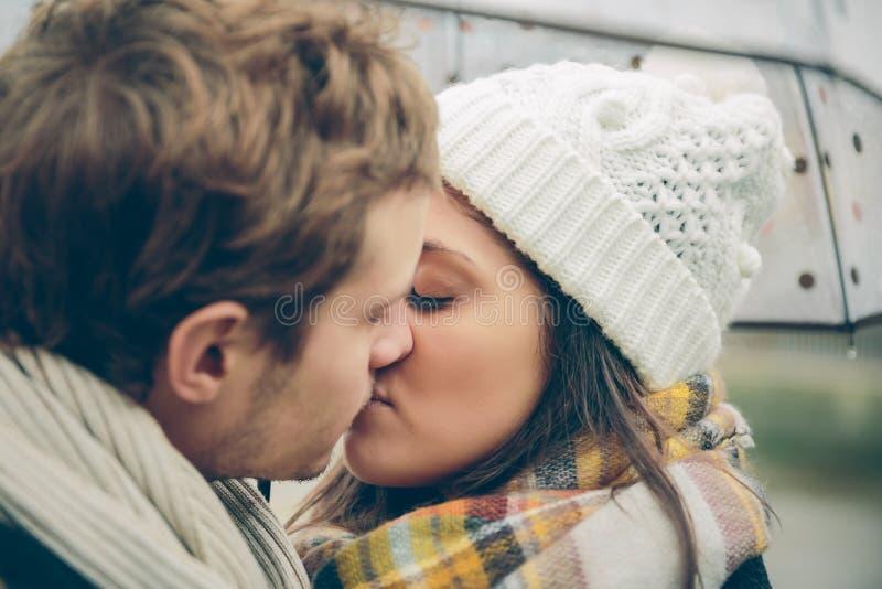Junge Paare, die draußen unter Regenschirm in a küssen stockfotografie
