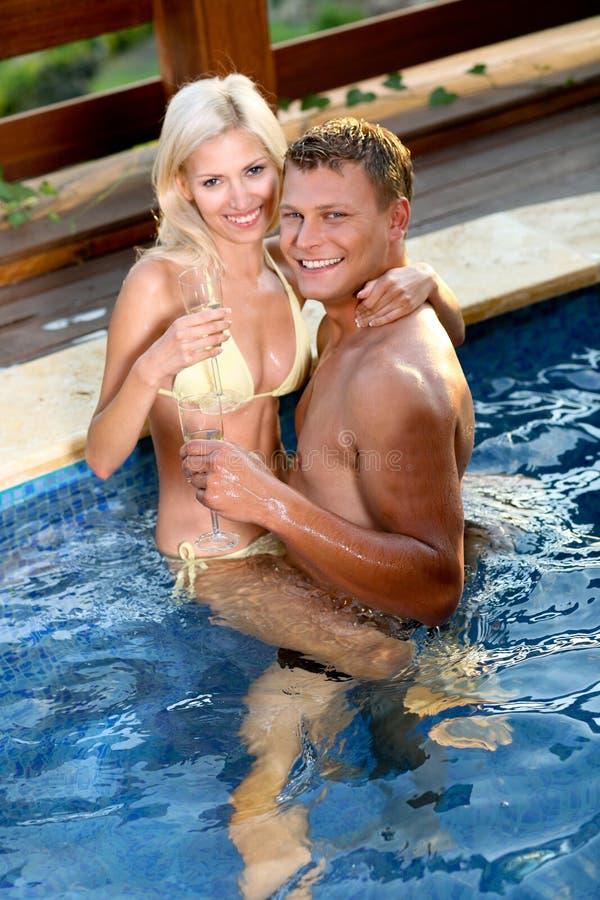 Junge Paare, die durch das Pool sich entspannen lizenzfreie stockfotografie
