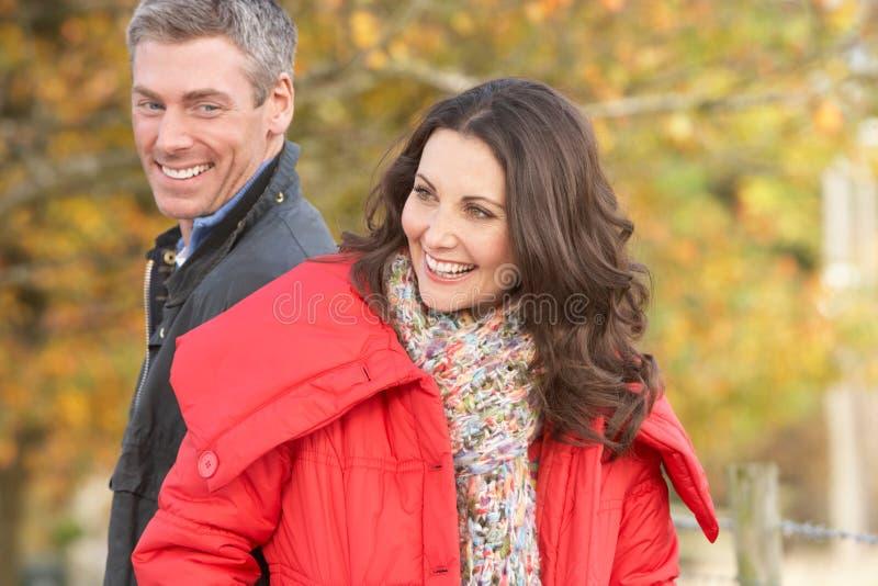 Junge Paare, die durch Herbst-Park gehen lizenzfreies stockbild