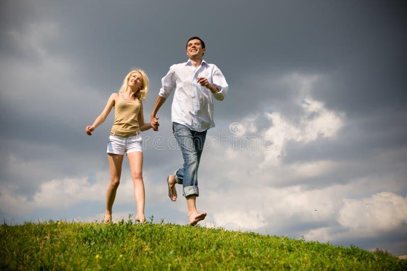 Junge Paare, die durch Sommerrasen gehen lizenzfreies stockfoto