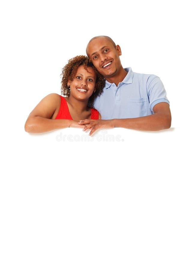 Junge Paare, die ein leeres Plakat halten. stockbilder