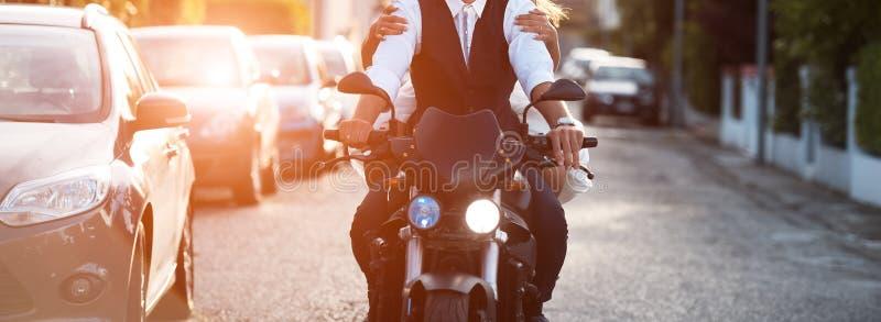 Junge Paare, die ein modernes Motorrad bei Sonnenuntergang reiten stockbilder