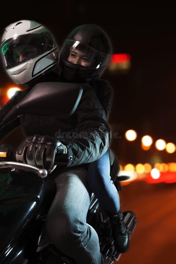 Junge Paare, die ein Motorrad durch die Stadtstraßen nachts in Peking reiten lizenzfreie stockbilder