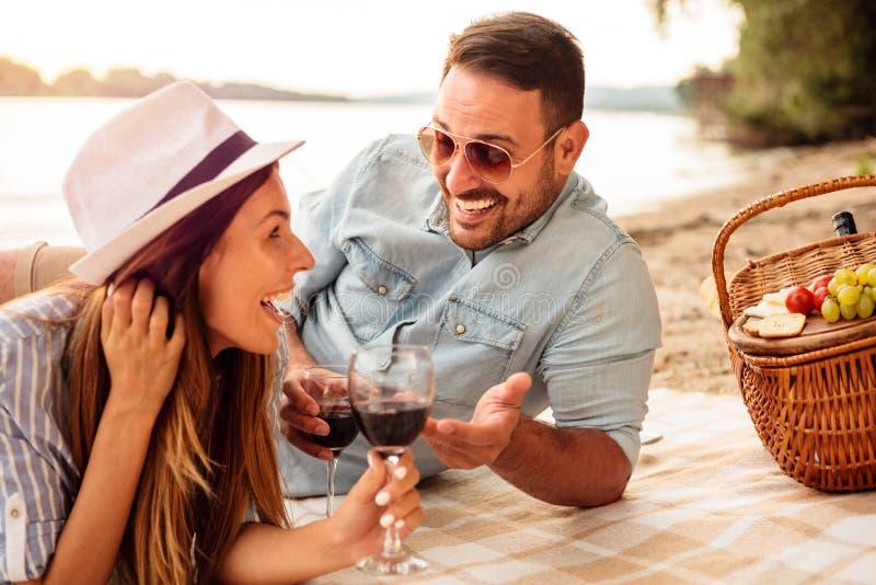 Junge Paare, die ein Picknick am Strand haben Lügen auf der Picknickdecke, dem trinkenden Wein und der Unterhaltung stockbilder