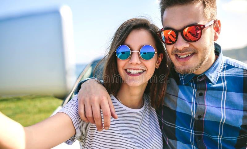 Junge Paare, die ein selfie auf dem Auto tun stockfotos