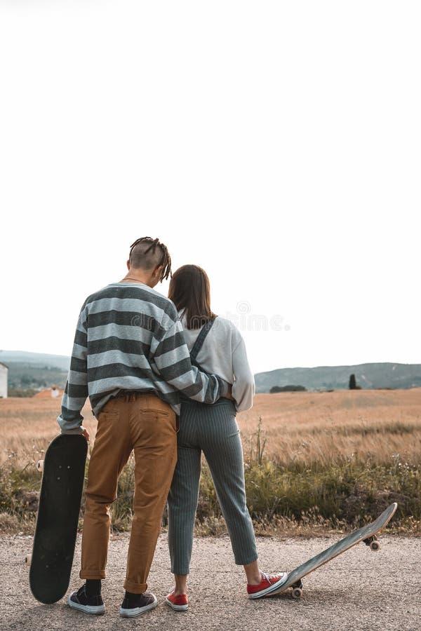 Junge Paare, die ein Skateboard auf eine Stra?e reiten Konzept von millenials Skateboardfahrern stockfoto