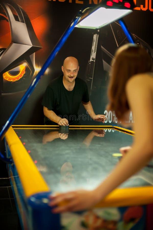 Junge Paare, die ein Spiel des Lufthockeys spielen lizenzfreie stockfotos