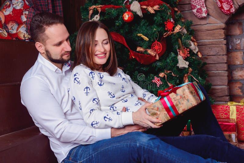 Junge Paare, die ein Weihnachtsgeschenk öffnen lizenzfreies stockfoto