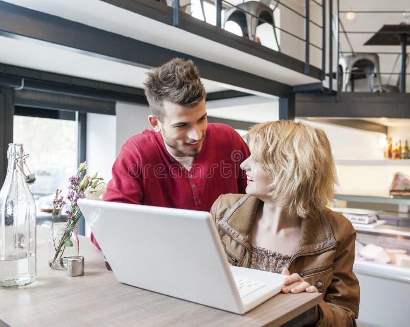 Junge Paare, die einander bei der Anwendung des Laptops im Café betrachten lizenzfreie stockfotografie