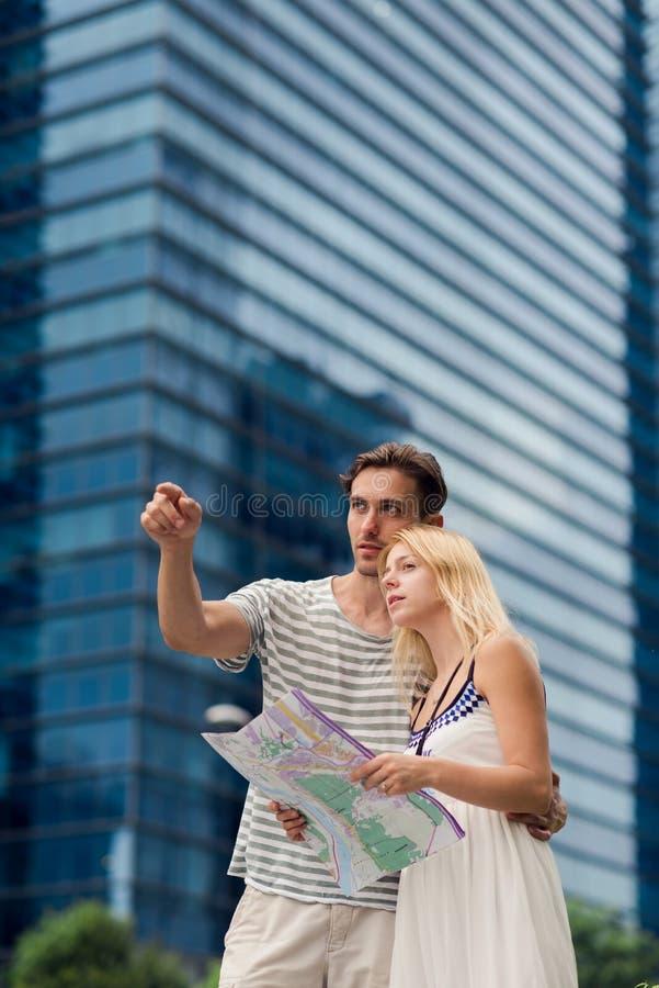 Junge Paare, die eine Karte beim Gehen durch eine moderne Stadt nahe Wolkenkratzern betrachten lizenzfreie stockfotografie