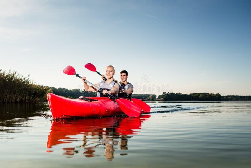 Junge Paare, die einen Kajak segeln lizenzfreies stockfoto