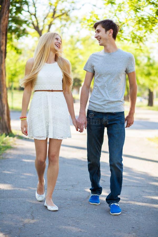 Junge Paare, die in einen Park gehen stockbilder