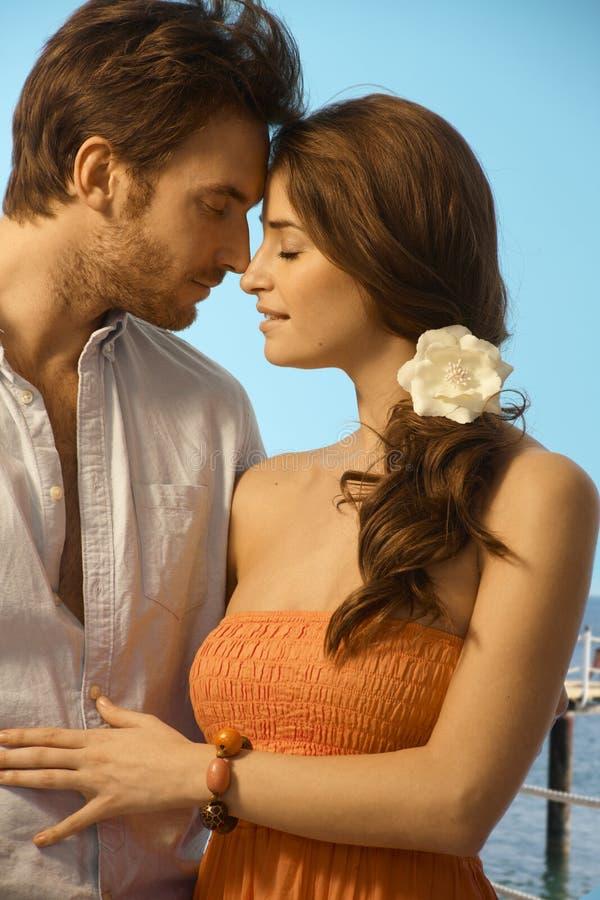 Junge Paare, die einen romantischen Feiertagsmoment haben lizenzfreie stockbilder