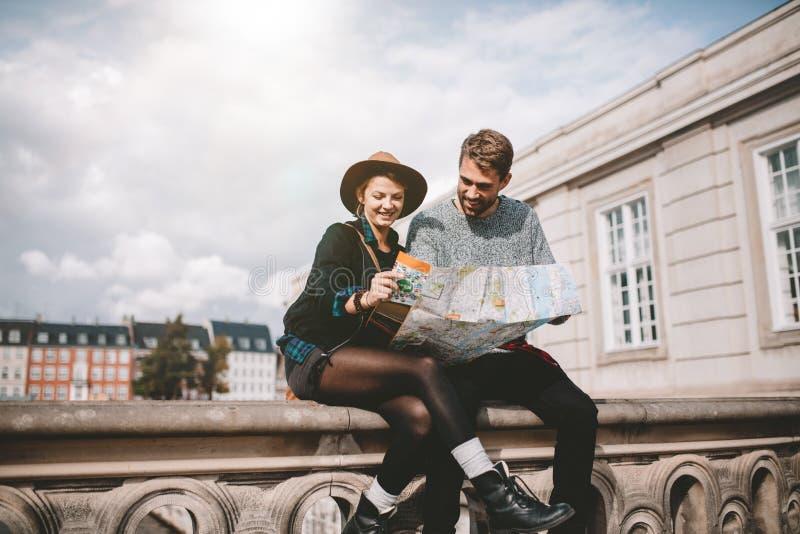 Junge Paare, die einen Stadtplan betrachten stockfotografie