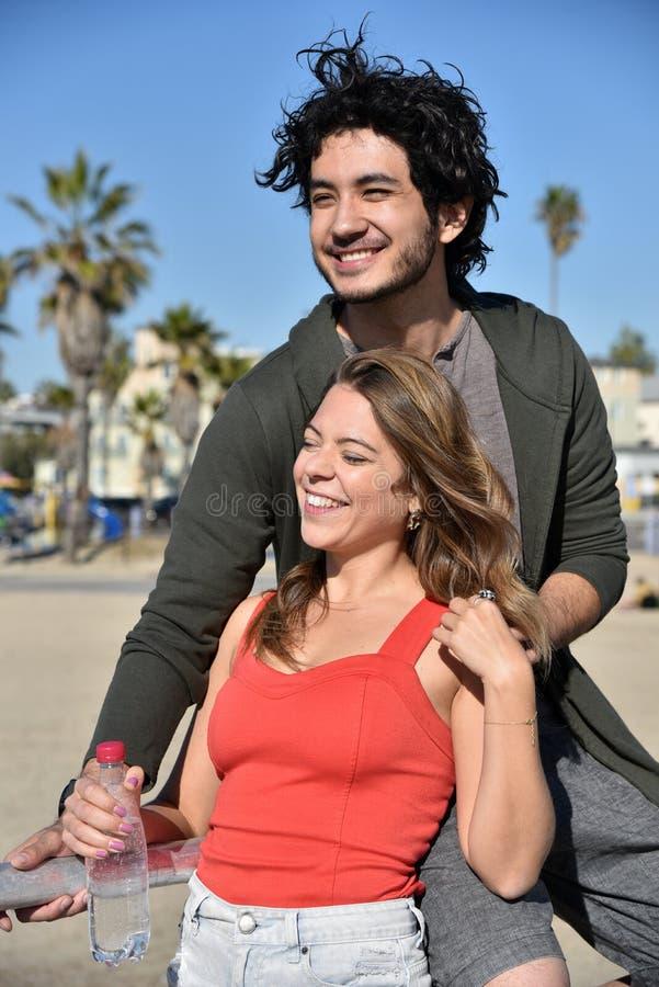 Junge Paare, die einen Tag auf dem Strand genießen lizenzfreie stockfotos