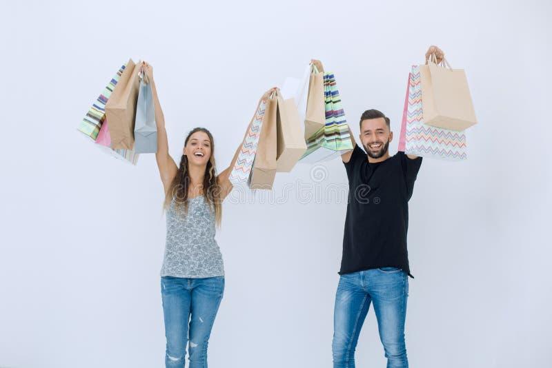 Junge Paare, die Einkaufstaschen halten und die Kamera betrachten stockbilder