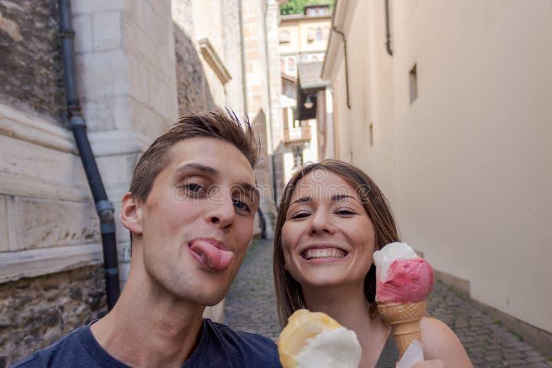 Junge Paare, die Eiscreme in einer Gasse essen lizenzfreie stockfotografie