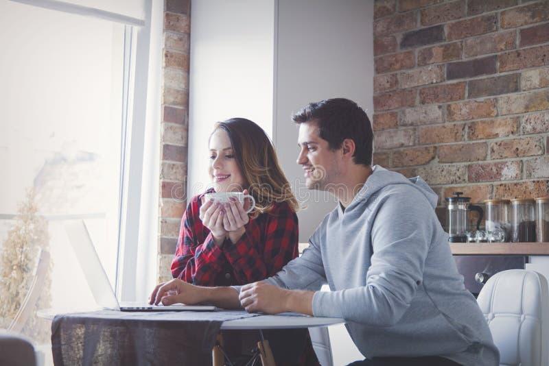 Junge Paare, die Familienbudget auf Laptop-Computer herstellen stockbild