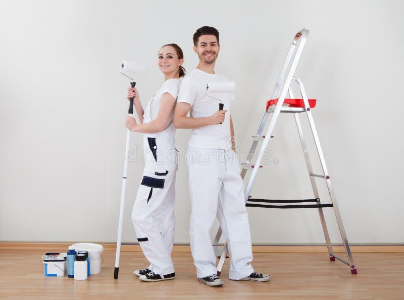 Junge Paare, die Farbenrolle halten lizenzfreie stockbilder