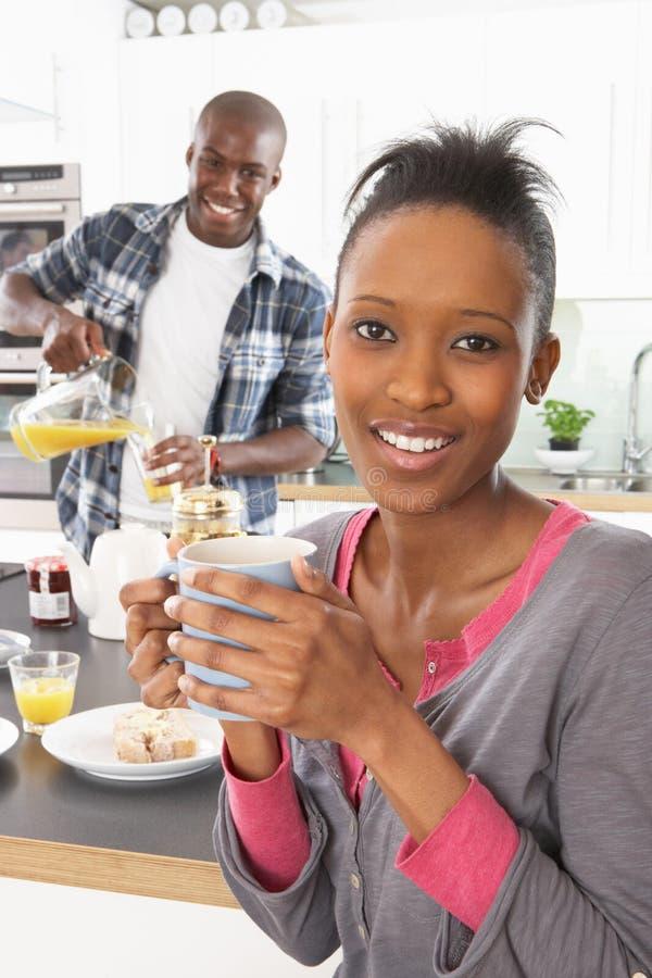 Junge Paare, die Frühstück in der modernen Küche zubereiten stockbilder