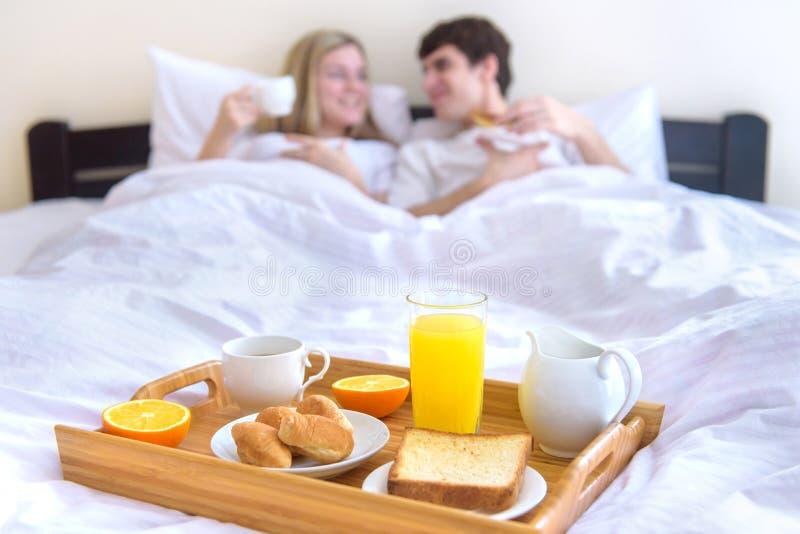 Junge Paare, die Frühstück im Bett essen lizenzfreie stockbilder