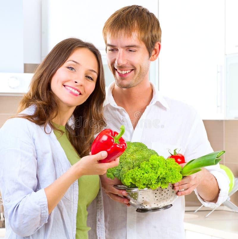 Junge Paare, die gesundes Lebensmittel kochen stockfotografie