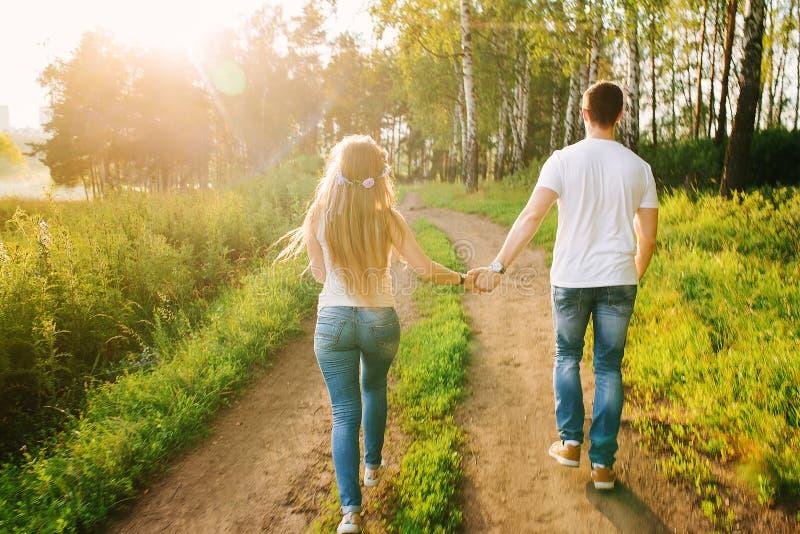 Junge Paare, die glücklich durch den Wald gehen lizenzfreie stockfotografie