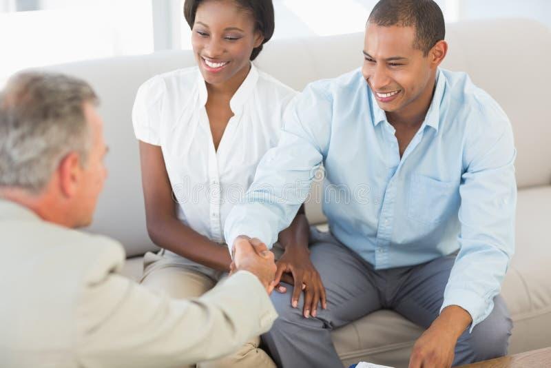 Junge Paare, die Hände mit Verkäufer auf dem Sofa rütteln lizenzfreies stockbild
