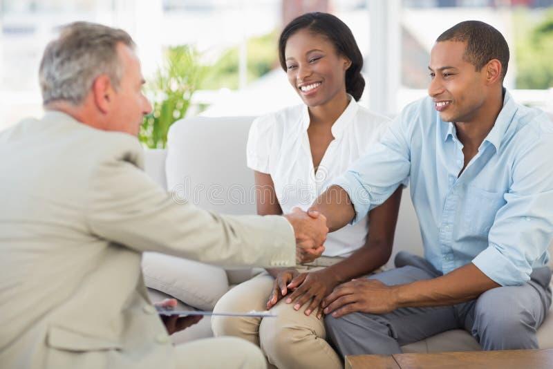Junge Paare, die Hände mit Verkäufer auf der Couch rütteln stockfoto