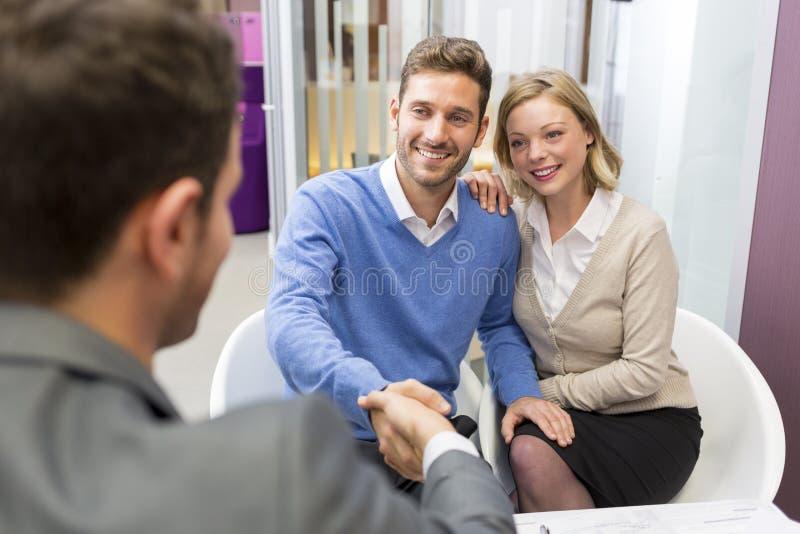 Junge Paare, die Handimmobilienagentur in der Niederlassung rütteln lizenzfreie stockfotos