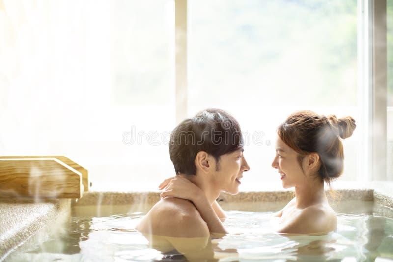 Junge Paare, die in heiße Quellen sich entspannen stockfotografie