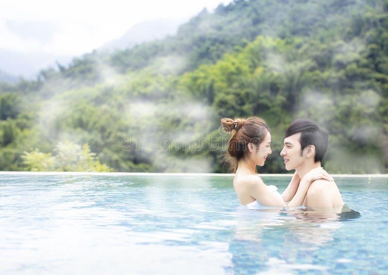 Junge Paare, die in heiße Quellen sich entspannen lizenzfreies stockbild