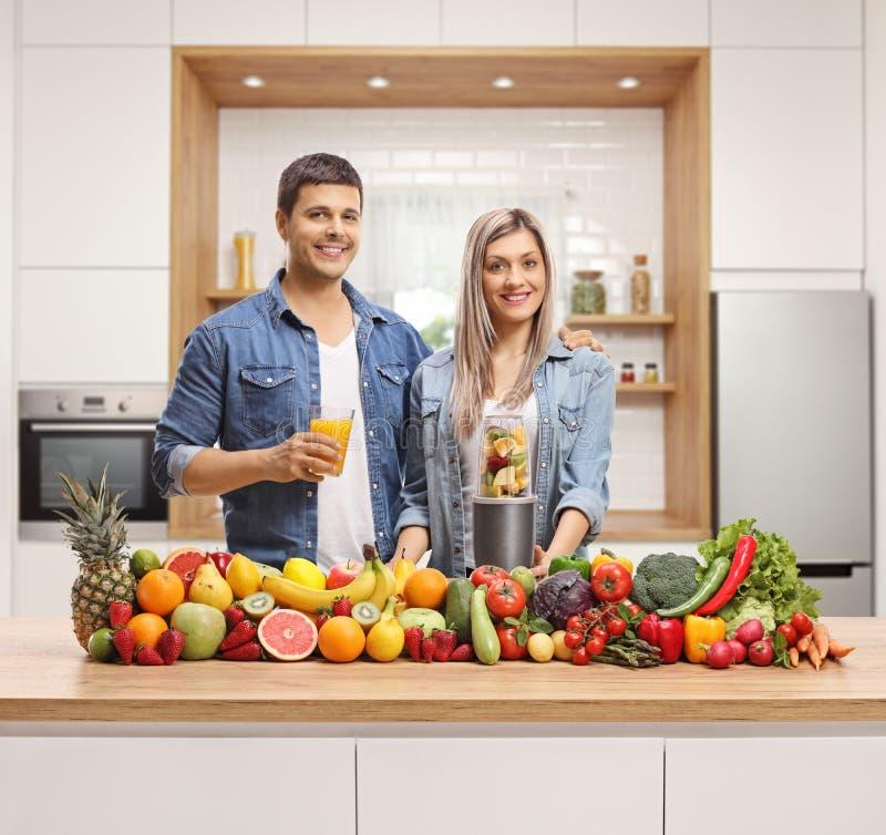 Junge Paare, die hinter einer Küchenarbeitsplatte mit Obst und Gemüse aufwerfen stockfotografie