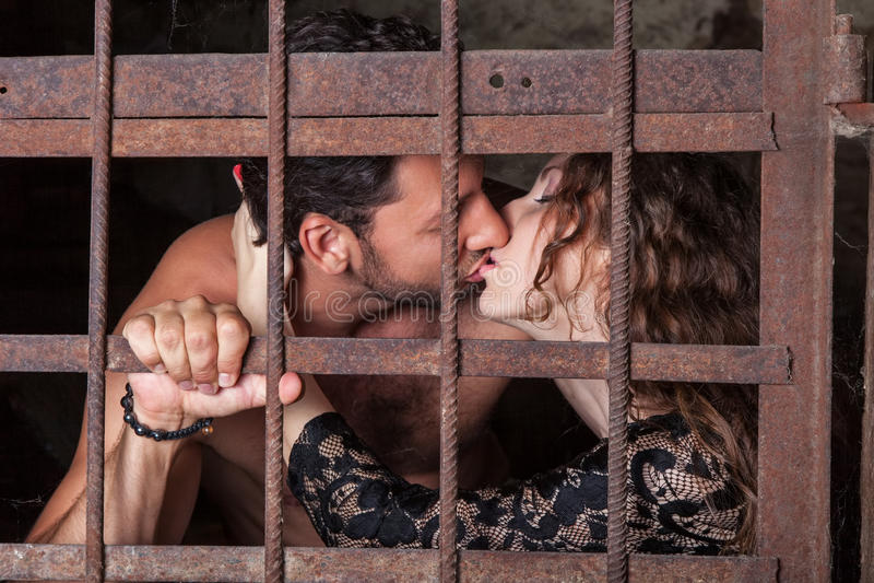 Junge Paare, die hinter Gittern küssen stockfotos