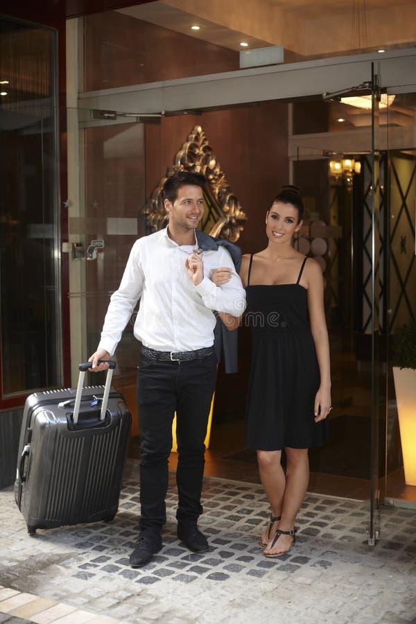 Junge Paare, die Hotel verlassen stockbild