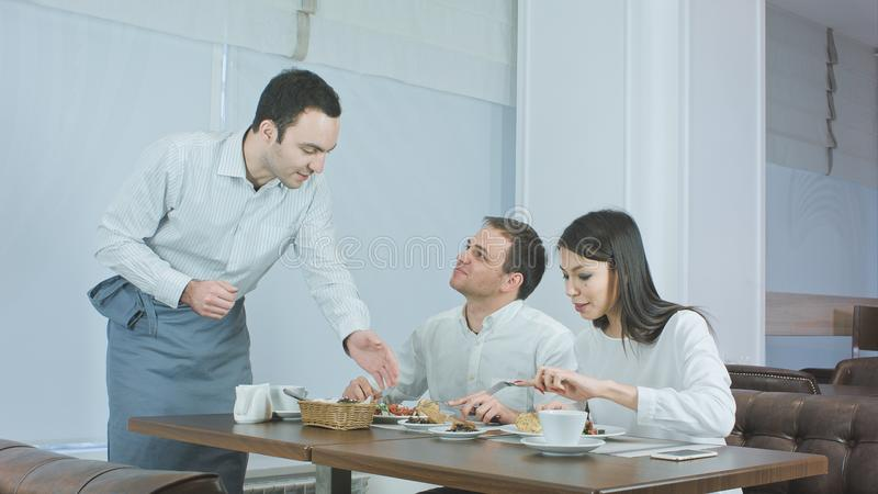Junge Paare, die ihr Mittagessen am Restaurant wenn Kellner holt mehr Lebensmittel genießen stockfotografie