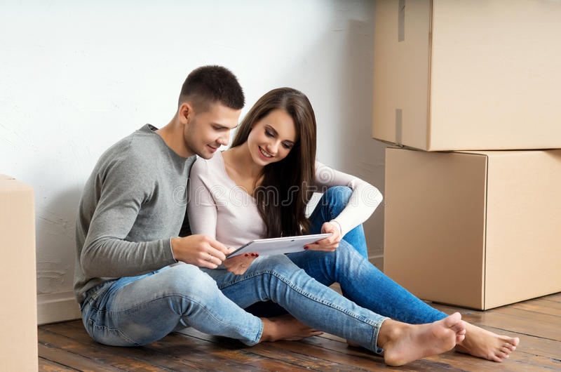 Junge Paare, die in ihrem neuen Haus unboxing sind lizenzfreies stockbild