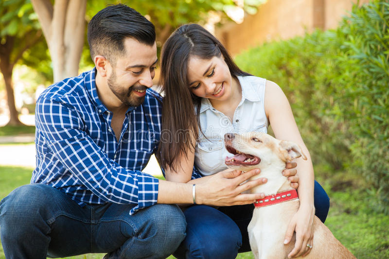 Junge Paare, die ihren Hund streicheln lizenzfreie stockfotografie