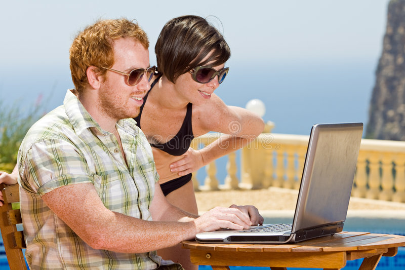 Junge Paare, die ihren Laptop betrachten stockbilder